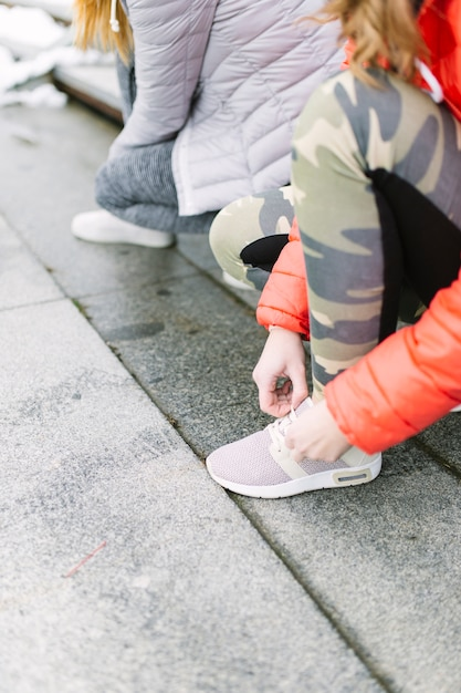 Close-up of two female runner tying shoelace Free Photo