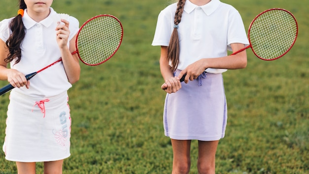 Close-up of two girls holding badminton in hand Free Photo
