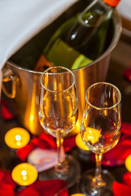 Close-up two glasses for champagne, candles and rose petals Premium Photo