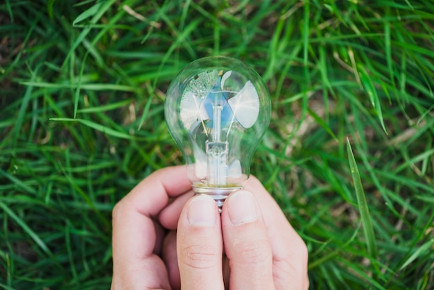 Close-up of two hands holding light bulb against green grass Free Photo
