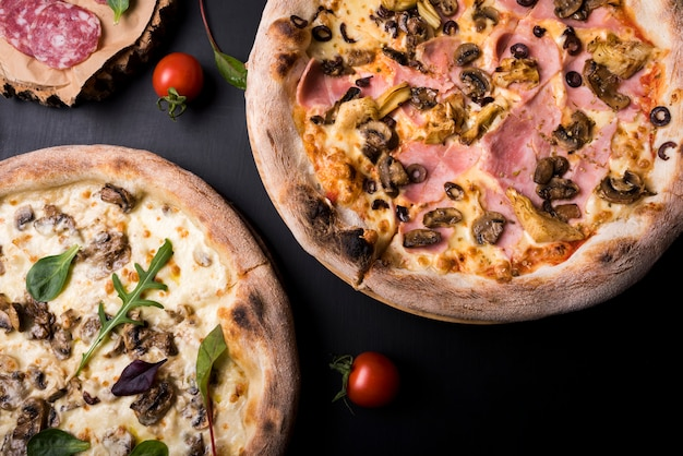 Close-up of two italian pizza with different toppings and cherry tomato Free Photo
