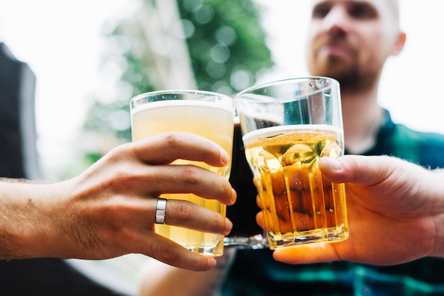 Close-up of two male friend's hand toasting glass of alcoholic drinks Free Photo