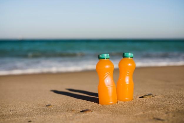 Close-up of two orange juice bottles near the seashore Free Photo