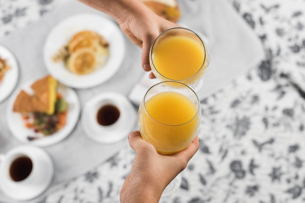 Close-up of two people's hand toasting glasses of orange juice Free Photo