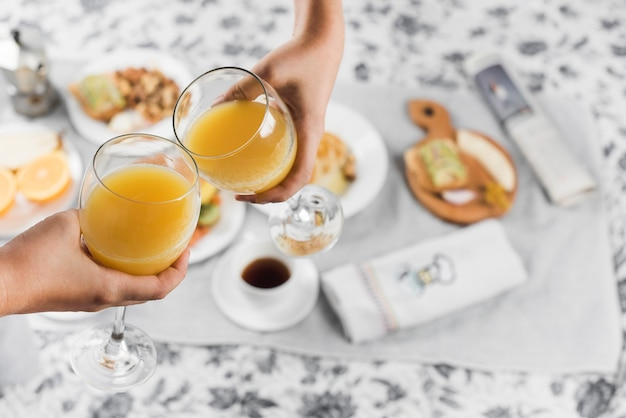 Close-up of a two people toasting juice glasses over the breakfast on table Free Photo