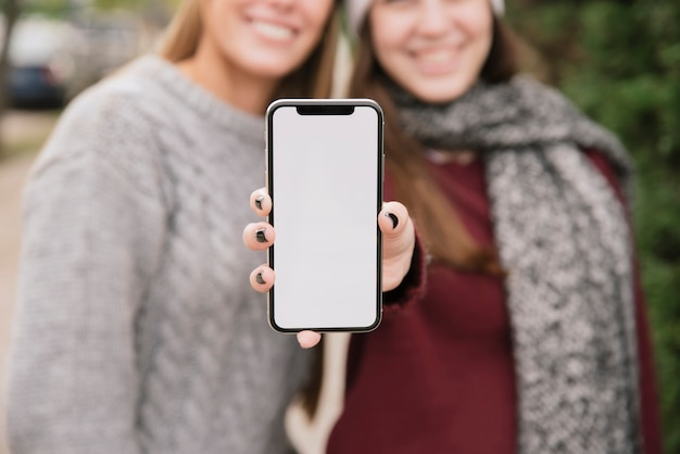 Close up two smiling women holding phone in hands Free Photo