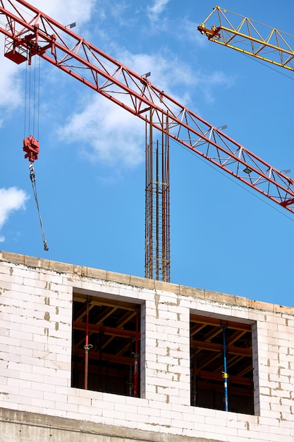Close-up of two tower cranes working against the backdrop of a new building and blue sky, selective focus Premium Photo