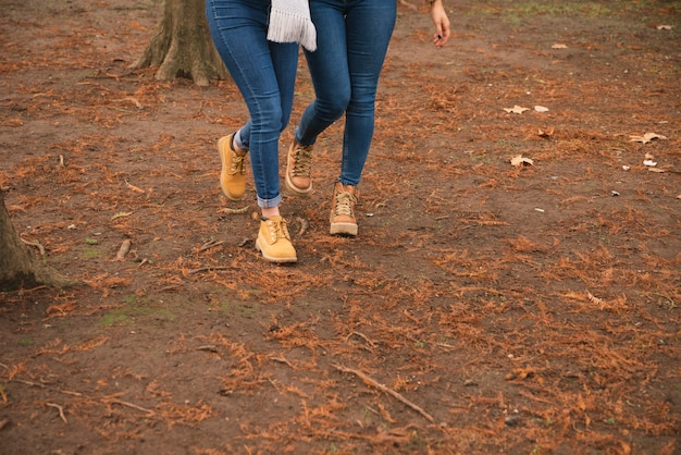 Close up of two women in boots walking in the park Free Photo