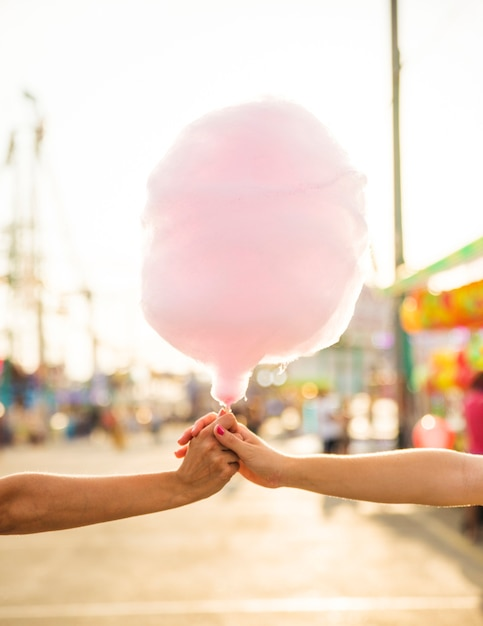 Close-up of two women's hand holding pink candy floss Free Photo