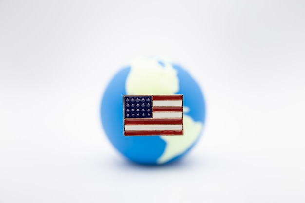 Close up of united state of america pin national flag over mini world ball on white Premium Photo
