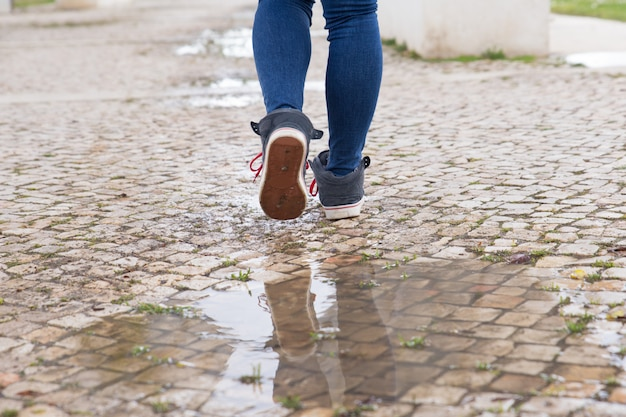 Close-up of unrecognizable woman walking on stone pathway Free Photo