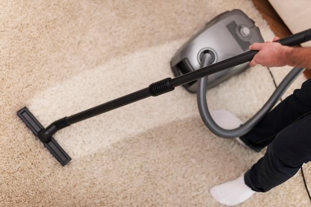 Primo piano di aspirapolvere un tappeto Foto Gratuite