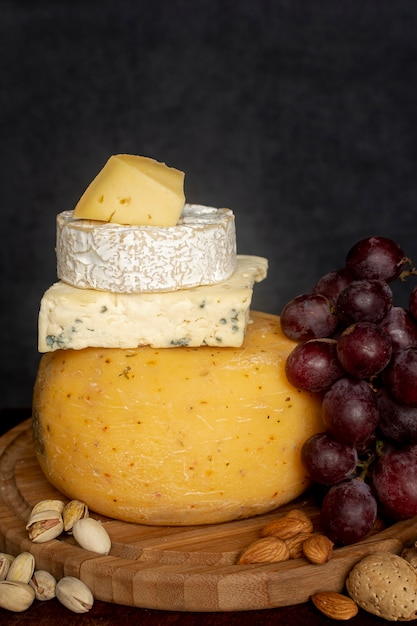 Close-up variety of cheese with grapes Free Photo