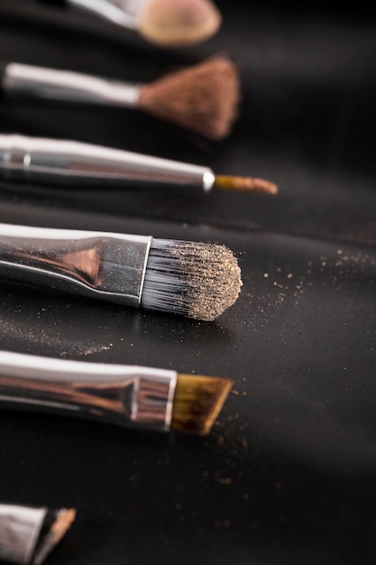 Close-up of various makeup brushes on black background Free Photo