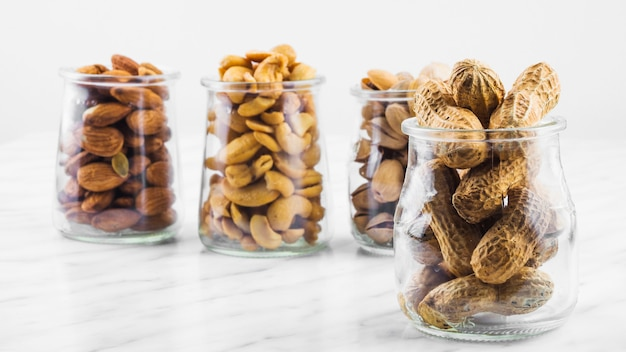 Close-up of various nut food jars on marble surface Free Photo