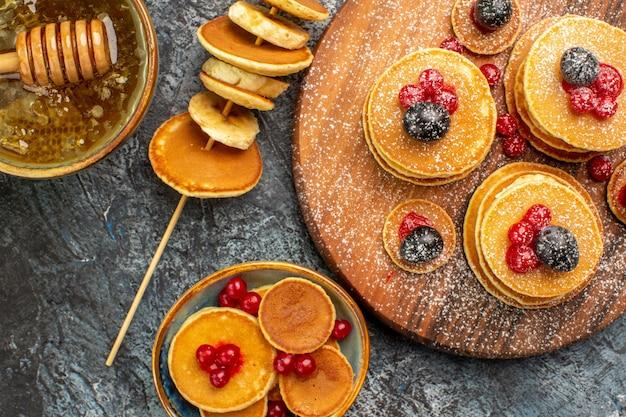 Vista ravvicinata di frittelle americane sul tagliere e miele con cucchiaio sul tavolo grigio Foto Gratuite