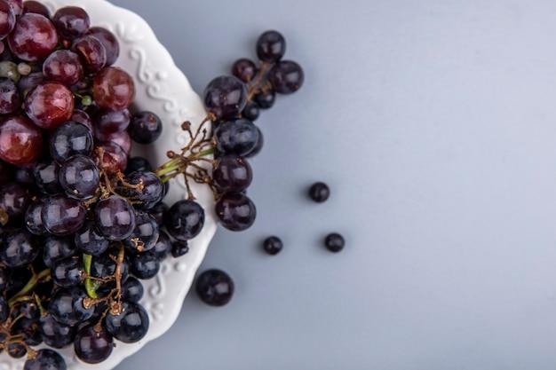Vista ravvicinata di uva nera e rossa nella piastra su sfondo grigio con spazio di copia Foto Gratuite