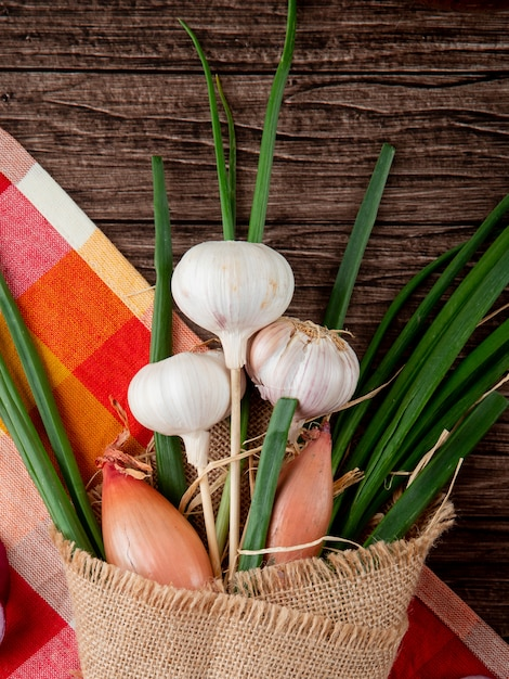Close-up view of bouquet of vegetables as garlic green onion and shallot on cloth on wooden background Free Photo