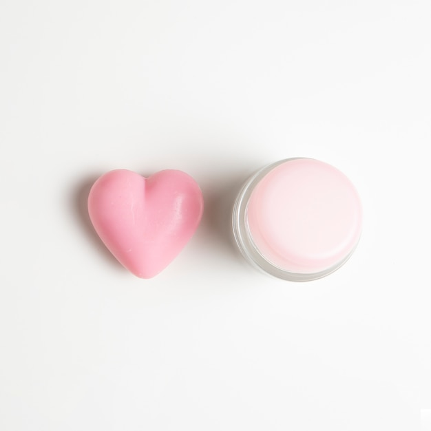 Close-up view of a cream and heart on white background Free Photo