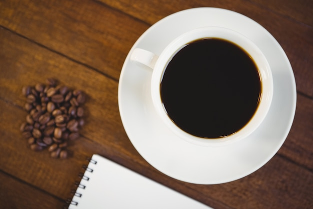 Close up view of cup of coffee and notepad Premium Photo