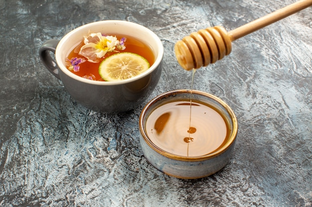 Vista ravvicinata di una tazza di tè con limone e miele su grigio Foto Gratuite