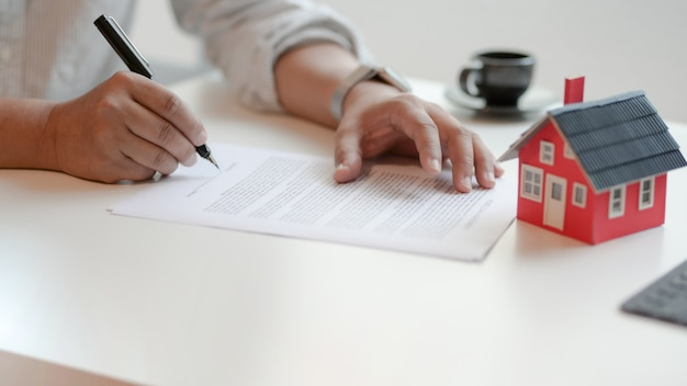 Close-up view of customer signing contract about home loan agreement Premium Photo