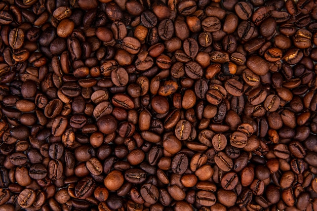 Close up view of dark fresh roasted coffee beans on coffee beans background Free Photo