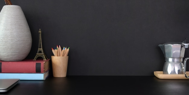 Close-up view of dark modern office room with decorations and copy space on black table and black wall Premium Photo