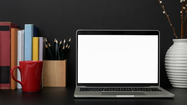 Close up view of dark modern workplace with blank screen laptop on black table Premium Photo