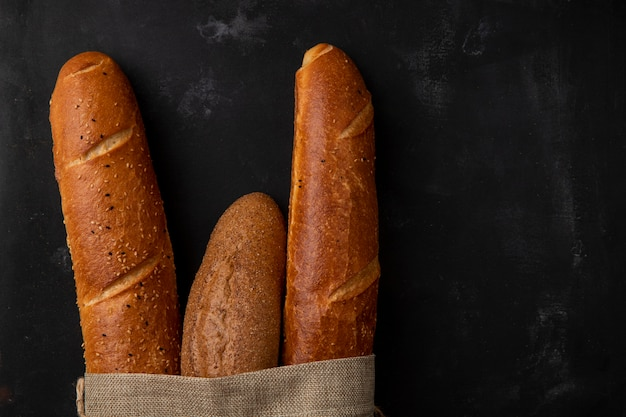 Close-up view of different types of baguette on left side and black background with copy space Free Photo