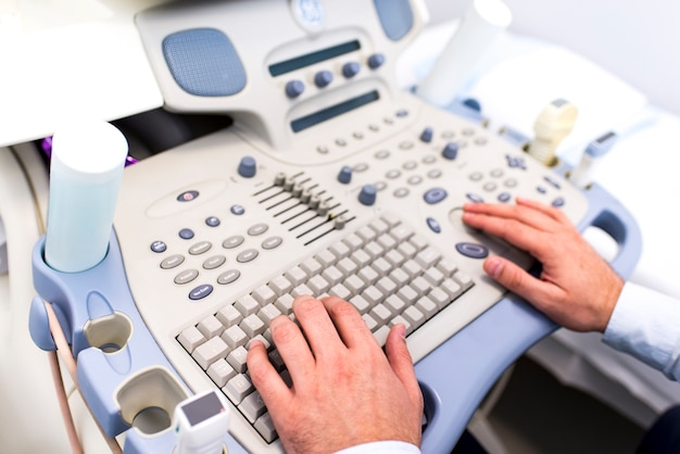 Close up view at doctors hands working on ultrasounds keyboard Premium Photo