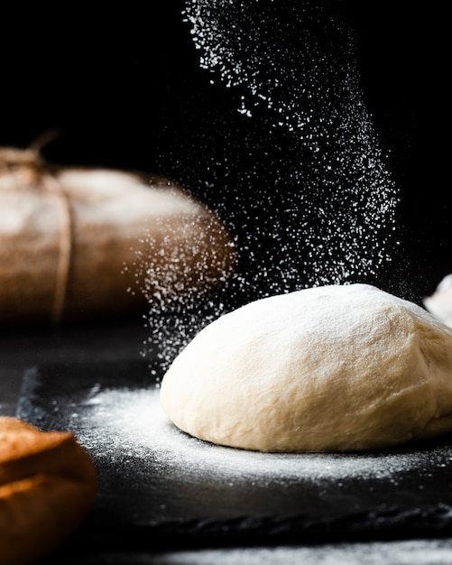 Close-up view of dough on black background Free Photo
