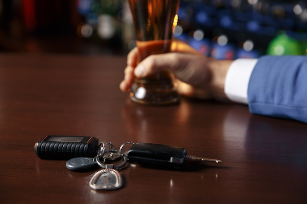 Close up view of drunk man giving car key to woman, on blurred background. don't drink and drive concept Premium Photo