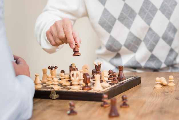 Close-up view of father hand and chess board on table Free Photo