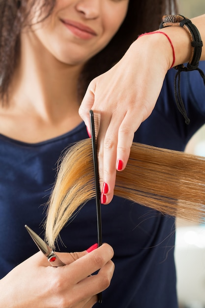 Close up view of female hairdresser hands cutting hair tips. keratin restoration, healthy hair, latest hair fashion trends, changing haircut style, shorten split ends, instrument store concept Premium Photo
