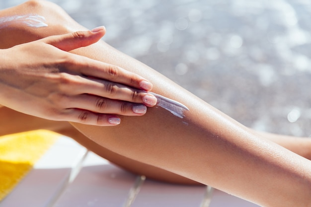 Close-up view of female hand applying sunscreen on her leg, near the sea. Free Photo