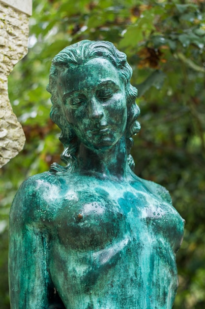 Close up view of a green statue of a naked woman. Premium Photo