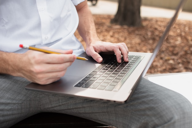 Close-up view of guy holding his laptop and a pencil Free Photo
