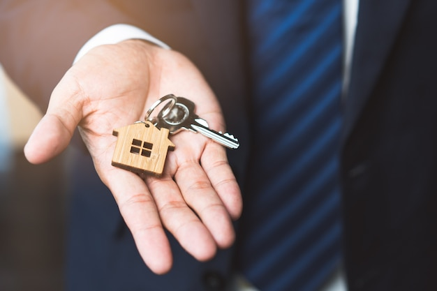 Close up view home keys in the agent hand giving to new owner. Premium Photo