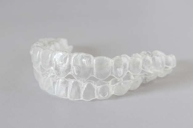 Close up view of invisalign braces or invisible retainers on grey , new orthodontic equipment Premium Photo