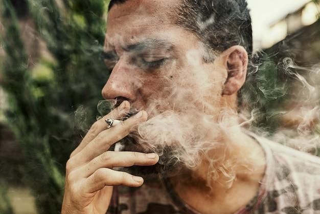 Close up view of man smoking marijuana cigarette outdoors Premium Photo