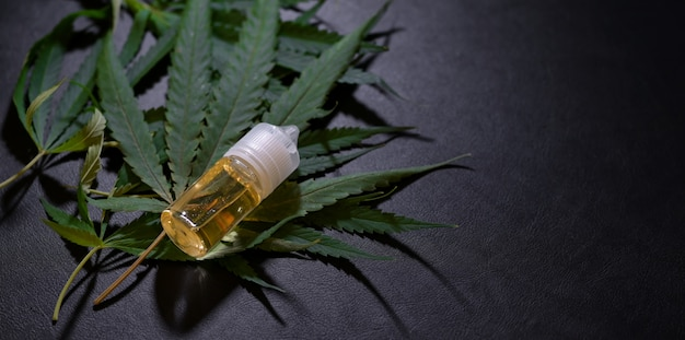 Close-up view of marijuana leaves and cannabis oil bottles Premium Photo