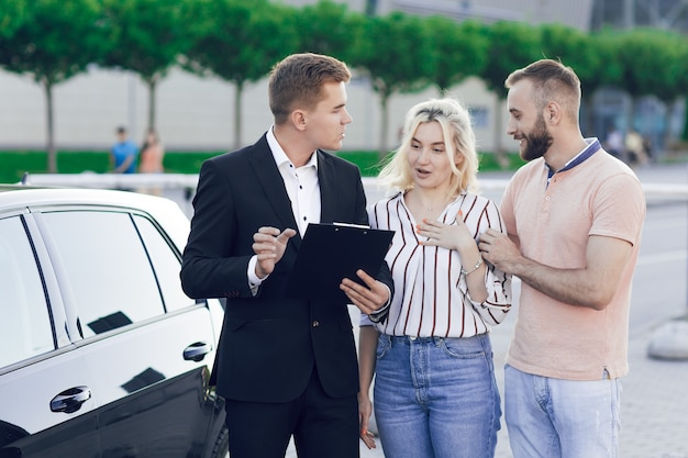 Крупным планом зрения продавца и молодой пары на открытом воздухе возле новой машины. продавец рассказывает молодой паре о машине. мужчина и женщина покупают машину. Premium Фотографии