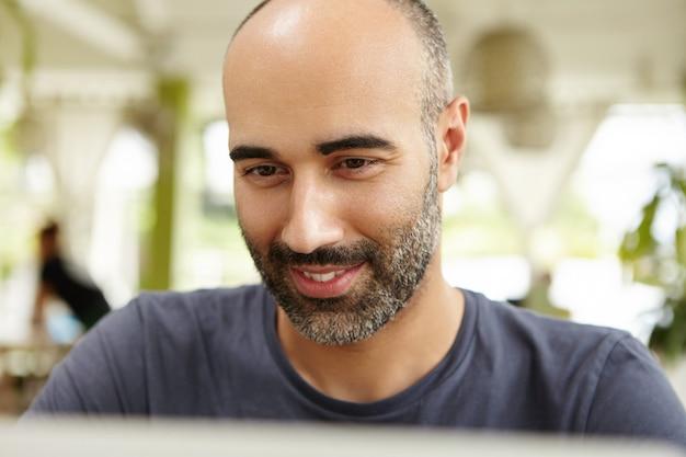 Крупным планом вид привлекательного взрослого мужчины с бородой, сидящего на открытой террасе, печатающего на ноутбуке, смотрящего на экран с заинтересованной улыбкой, использующего wi-fi для общения в интернете во время отпуска Бесплатные Фотографии