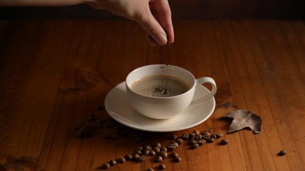コーヒー豆で飾られた木製のテーブルの上のカップにコーヒーパウダーを追加するバリスタの手のクローズアップ表示 Premium写真