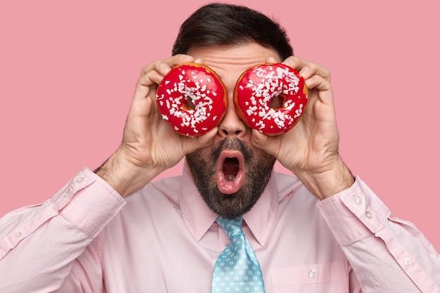 수염 난 남자의 뷰를 닫습니다 눈에 빨간 도넛을 유지하고 입을 넓게 열어 둡니다. 무료 사진