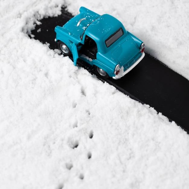 Крупным планом вид голубой игрушечный автомобиль со снегом Бесплатные Фотографии