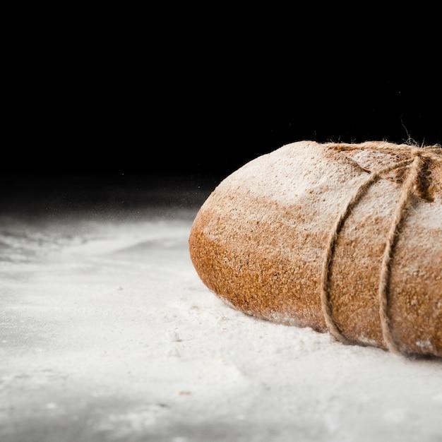 黒の背景にパンと小麦粉のクローズアップビュー 無料写真