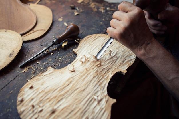 Крупным планом вид рук плотника, формирующих и вырезанных из дерева в своей старинной мастерской Бесплатные Фотографии