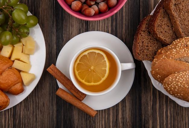 Крупным планом чашка горячего тодди с корицей на блюдце и орехами с сырным виноградным круассаном и тарелкой ломтиков хлеба на деревянном фоне Бесплатные Фотографии